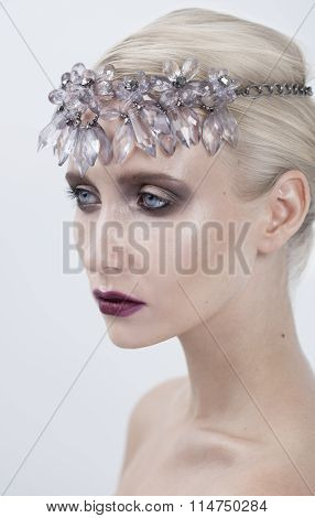 young fashion woman with bright makeup, lady winter with ice crystal diadem. cold concept on face