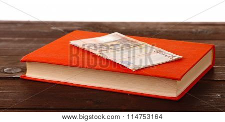 Red book with euro banknotes on white background. Stash of money