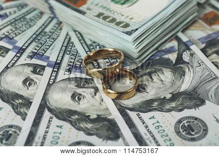 Wedding rings on money background, close up
