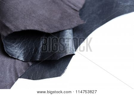 Black leather front and wrong side texture on white background, close-up