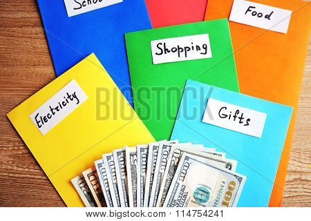 Colourful envelopes with money for needs on wooden background
