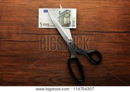 Concept of spending money - scissors cut money on wooden background