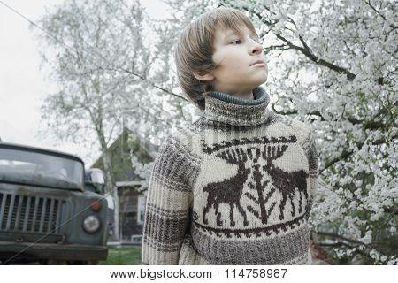 Looking ahead teenager in woolly vintage deer sweater outdoors in blooming fruit garden at old log h