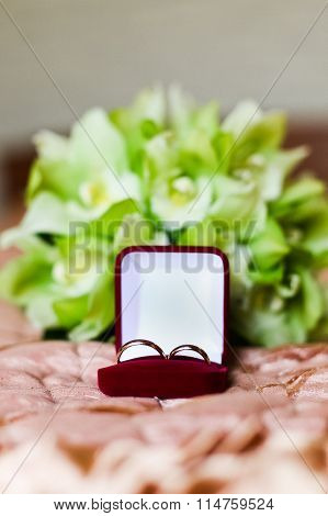 Wedding Rings In Red Box On The Green Bouquet