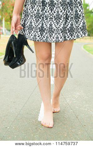 Classy woman wearing fashionable skirt walking barefeet on asfalt surface carrying high heels, visib