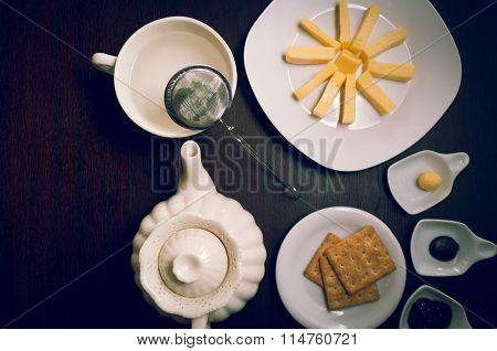 Cup of tea, hot water decanter, cheese, crackers and selection marmelades as seen from above