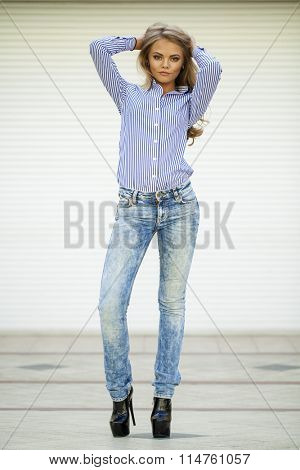 Portrait of pretty young blonde woman in blue jeans