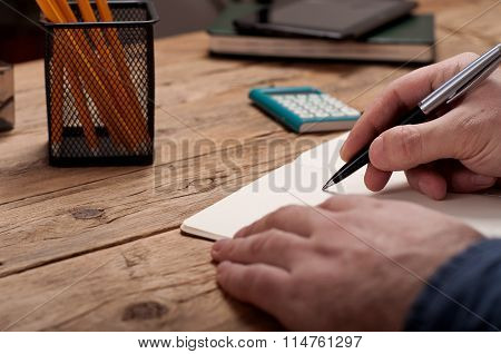 Closeup Of A Young Man Writes  In A Notebook