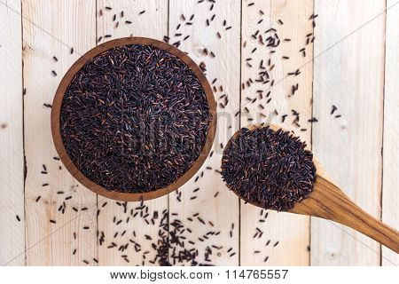 Top View Of Rice Berry Rice With Wooden Bowl And Spoon On Wooden Table(rice Berry Is Crossbreed Betw