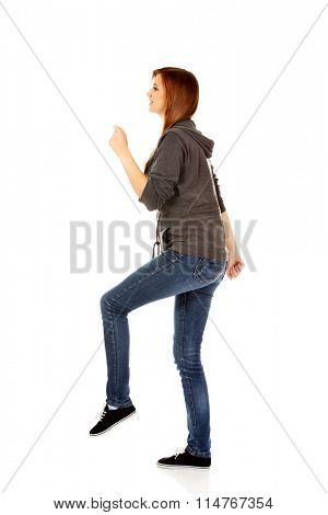 Teenage woman trying to trample something