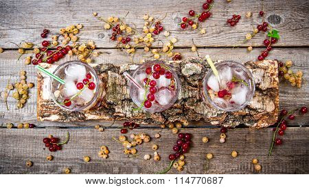 Three Wild Currant Cocktail With Ice On A Wooden Table.