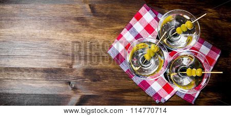 Three Martini With Olives On A Wooden Table. Free Space For Text.