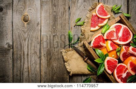 Sliced Grapefruit On The Board With A Full Box And Leaves.