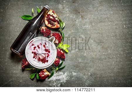 The Pomegranate Juice In A Bottle With The Juice And Slices Of Ripe Pomegranate.