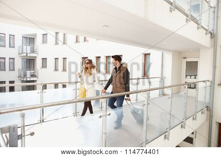 Young couple leaving apartment house with small luggage hand in hand.
