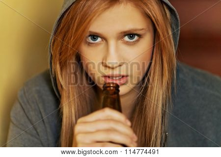 Teenage depressed woman sitting on the staircase and drinking a beer