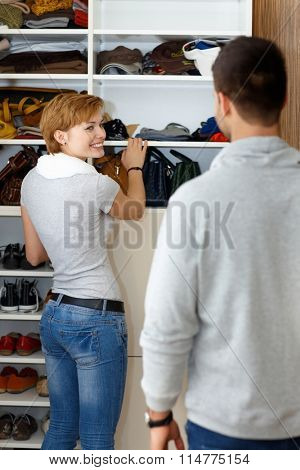 Young woman packing in walk-in closet, smiling to husband.