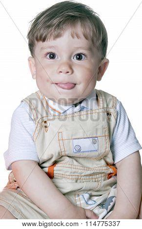 Amusing little boy showing tongue