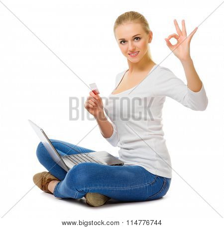 Young girl with laptop and plastic card isolated