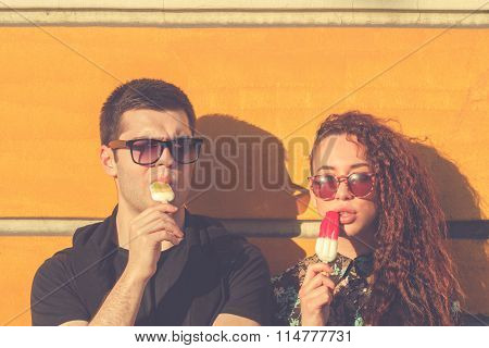 Urban couple outdoors eating ice-cream on the street.