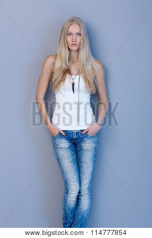 Beautiful young scandinavian woman standing against blue wall in jeans and top with hands in pockets, looking at camera serious.