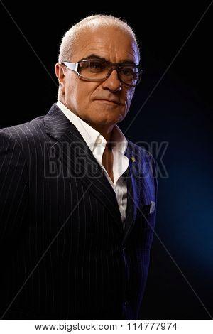 Closeup portrait of confident mature businessman in elegant suit, looking at camera.