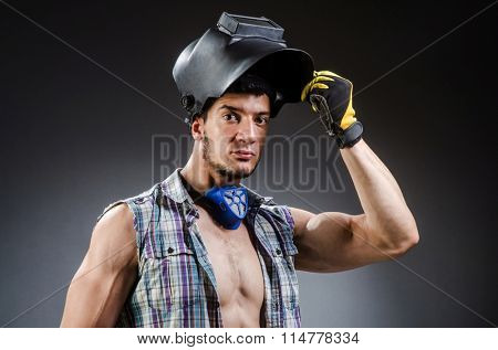 Welder with mask against dark background