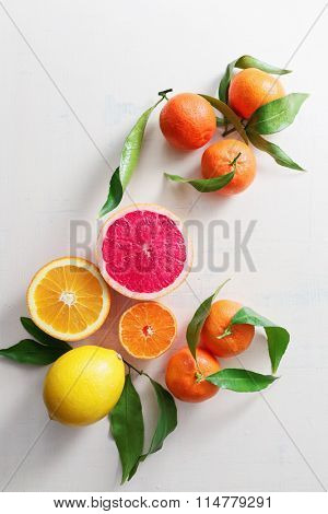 Fresh citrus fruits with leaves on table