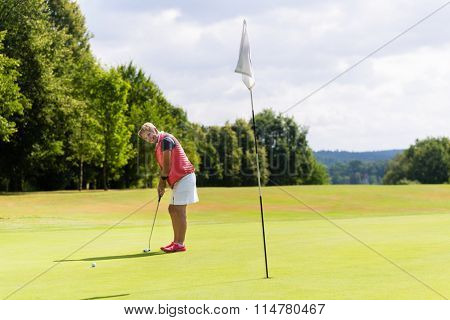 Senior woman playing golf putting on the green