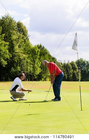 Senior man practicing golf with teacher helping