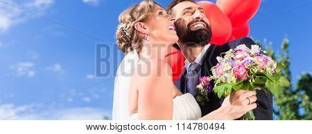Bride and groom at wedding with read helium balloons