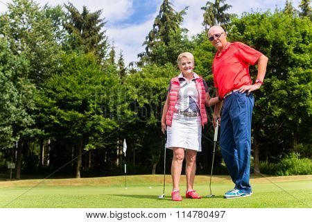 Senior couple playing golf in their leisure time