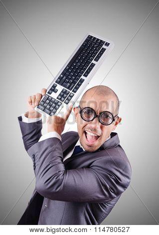 Nerd businessman with computer keyboard against gradient