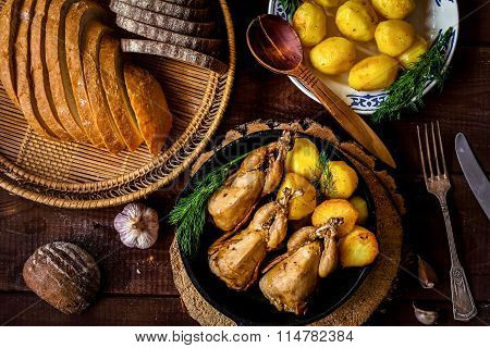 Roasted quails, golden baked potatoes and variety of bread. Dinner meal
