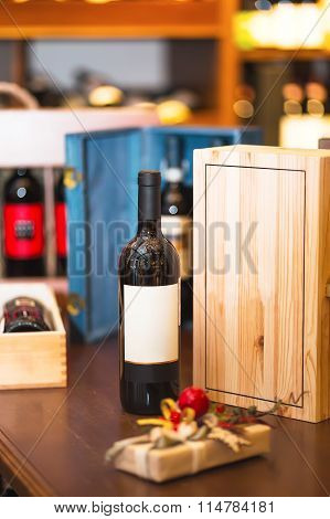 Bottle of red wine in the wine room. Against the background of wooden boxes. Gift for holiday
