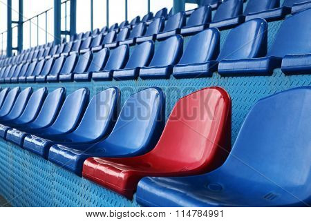Empty plastic seats at stadium, open door sports arena.