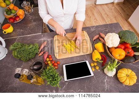 Woman preparing vegetarian lunch from recipe on tablet