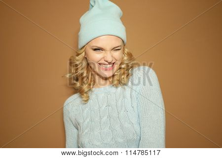 Gorgeous young woman with blond ringlets in a green knitted winter outfit blinking her eye