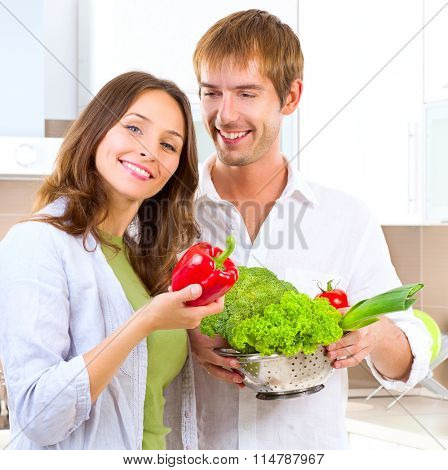 Young Couple Cooking Healthy food at home. Diet. Man and Woman in their Kitchen at home Preparing Dinner - Vegetable Salad. Dieting. Healthy vegetarian food, vegan. Family