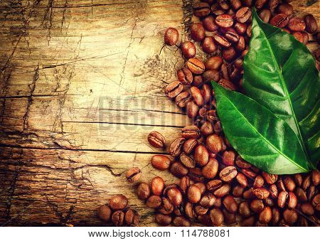 Coffee Beans over Wood Background. Coffee border design over old cracked wooden table. Leaves and roaster beans