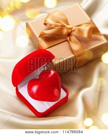 Valentine Heart and Gift box on Golden Silk Background. Holiday backdrop. Romantic St. Valentine's Day card design. Red velvet Gift Box with a heart on silk. Love