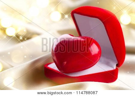 Valentine Heart in Gift box on Golden Silk Background. Holiday background. Romantic St. Valentine's Day card design. Red velvet Gift Box with a heart on smooth satin. Love