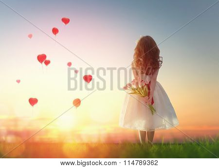 Sweet child girl looking at red balloons. Little child girl holding bouquet of flowers. Balloons in