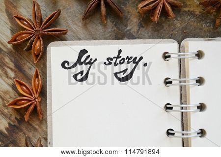 An empty retro spiral notebook with old paper with a note that says My Story and anise stars on wood