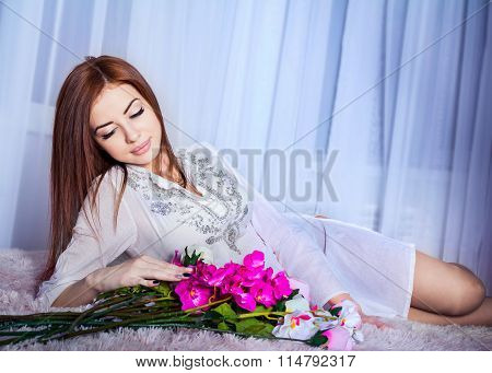 Pretty woman laying with flowers