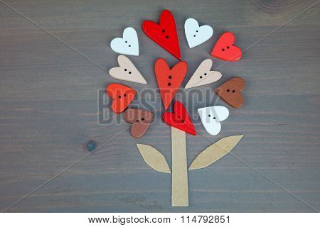 Button love tree on grey wooden background.