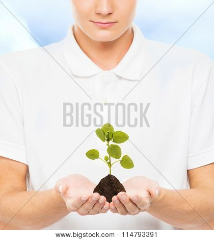 Young and handsome teenage boy holding soil with a plant on cloudy sky background. Ecology concept.