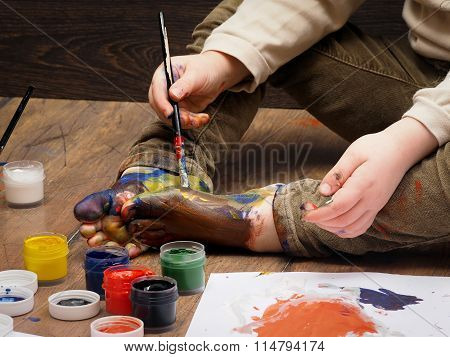 A child paints paint bare feet