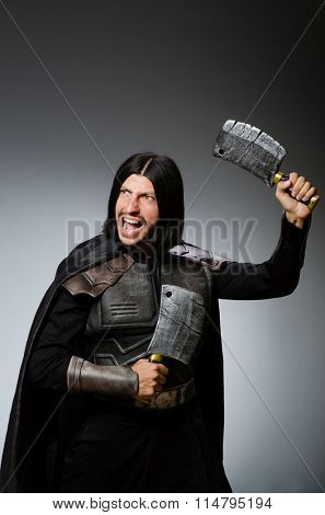 Knight with axe against dark background