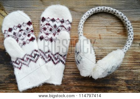 Soft woolen mittens with winter headphones on wooden table